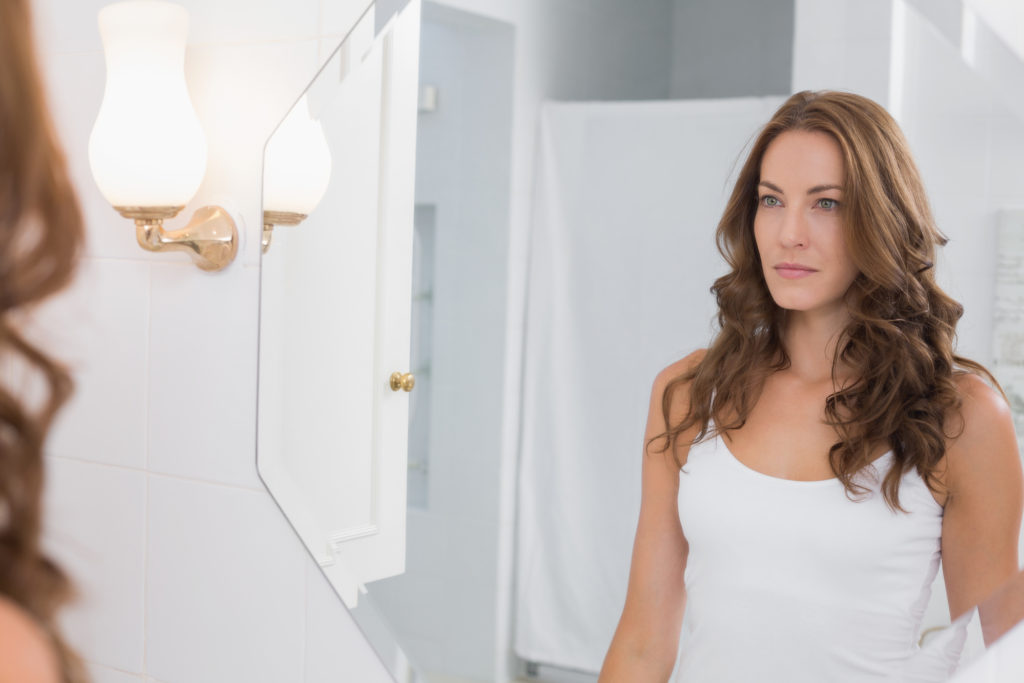 Serious beautiful young woman looking at herself in the bathroom mirror at home